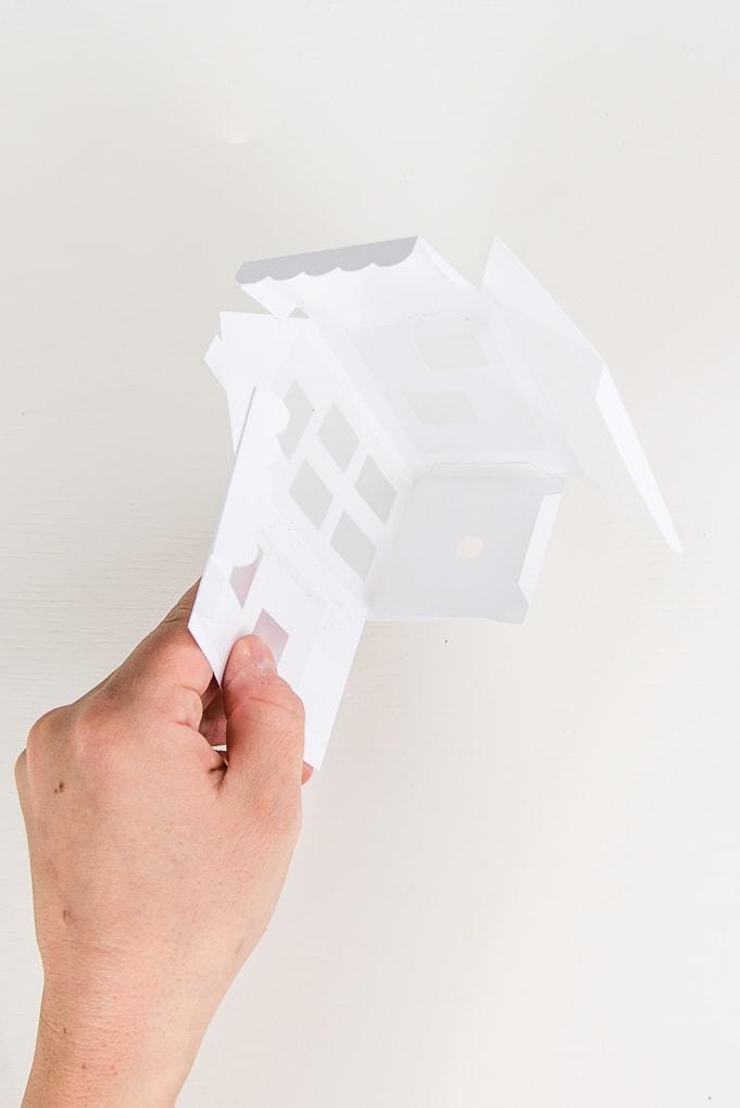 hand assembling paper 3D winter house walls