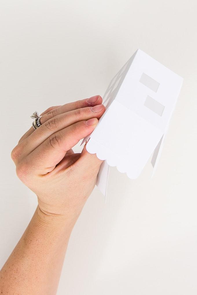 hand assembling paper 3D winter house roof