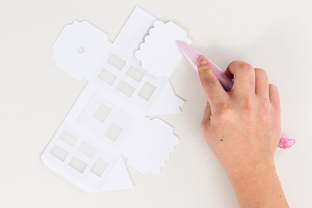 hand folding paper 3D winter house with bone folder roof