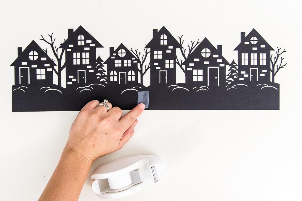 taping winter night hurricane vase paper cutouts