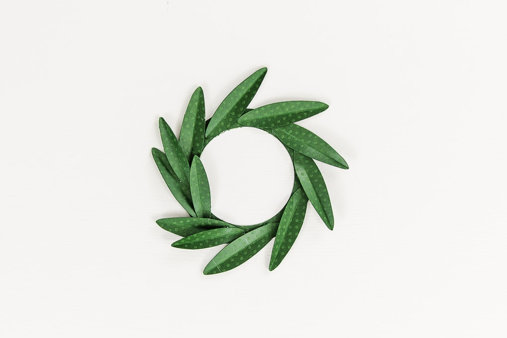 layering green paper leaves on wreath base