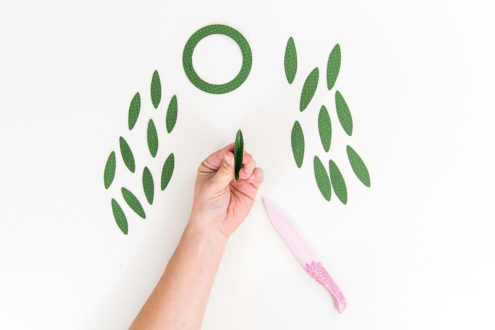 hand folding green paper leaves