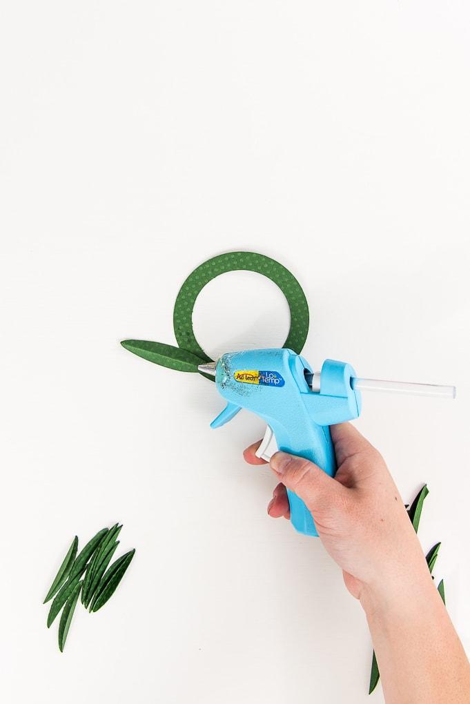 hot glue gun attaching green paper leaf to wreath base