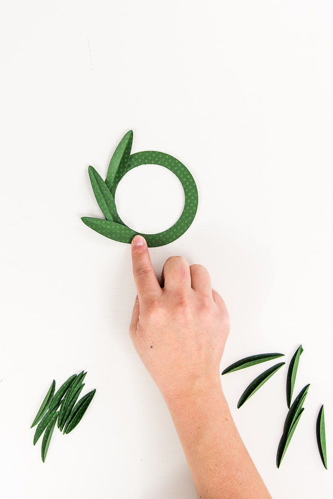 hand attaching green paper leaf to wreath base