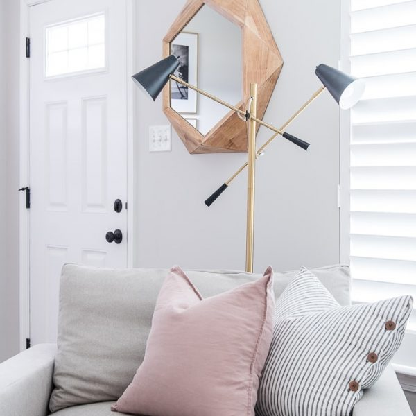 Ella modern accent lamp from Brighttech behind an reading chair with pillows
