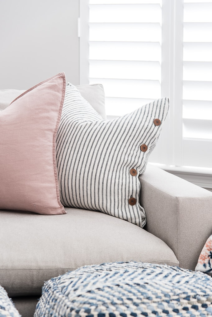pink throw pillow and blue striped throw pillow on the harmony oversized chair and a half from west elm