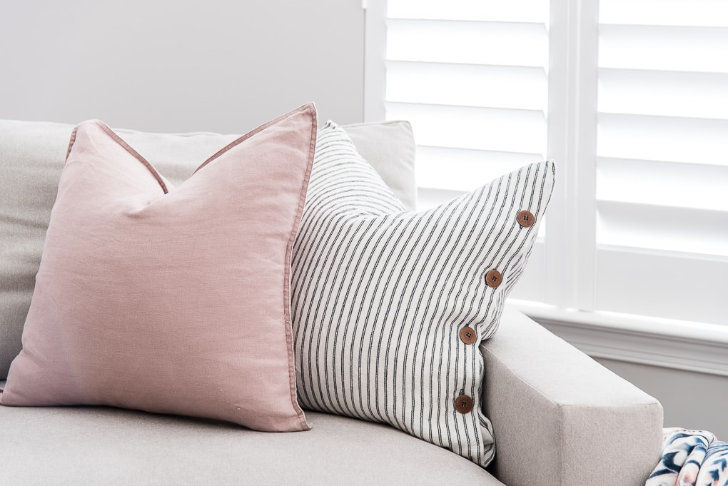 pink and blue striped throw pillows on the harmony oversized chair and a half from west elm
