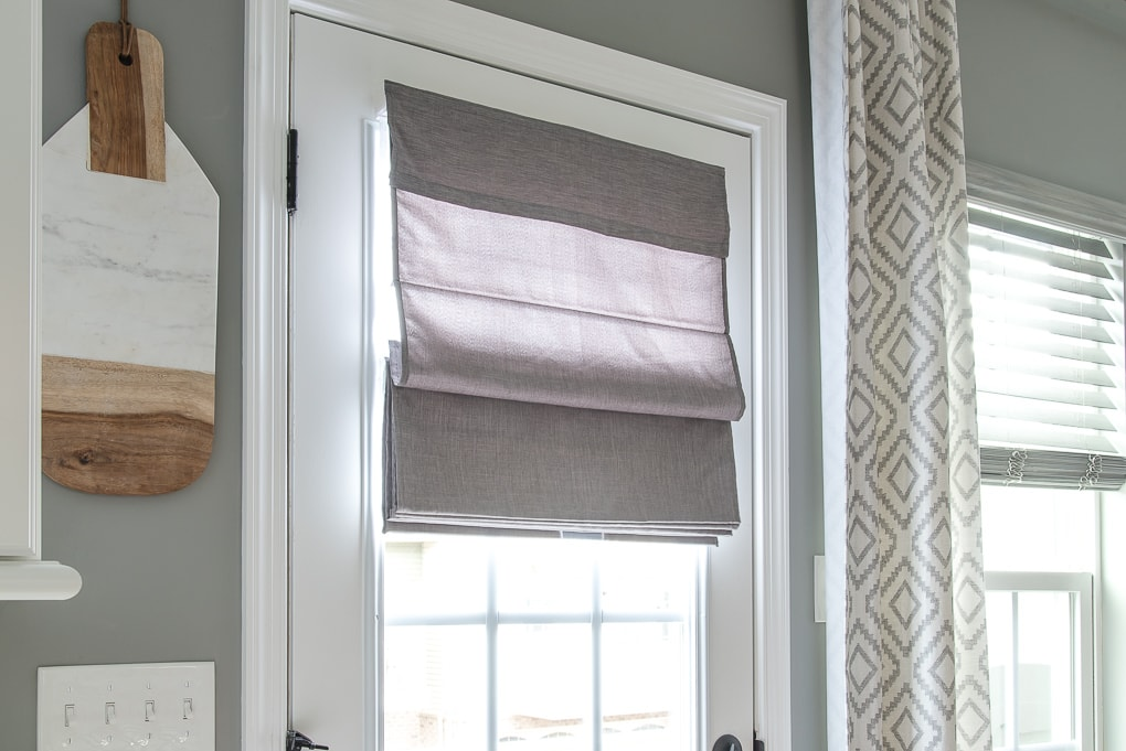gray roman shade on a french door with light filtering outside mount