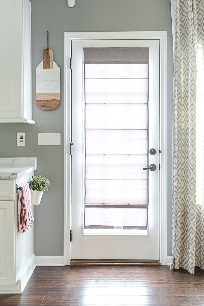 gray roman shade on a french door with light filtering outside mount fully extended