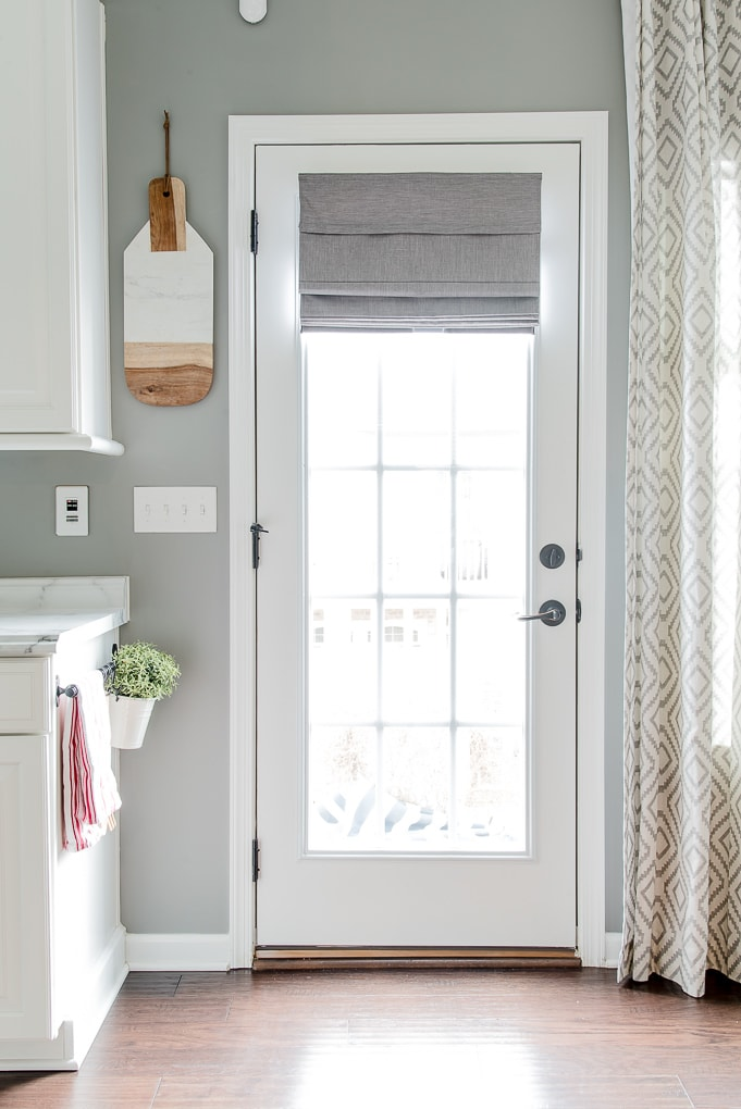 gray roman shade on a french door with light filtering outside mount partially extended