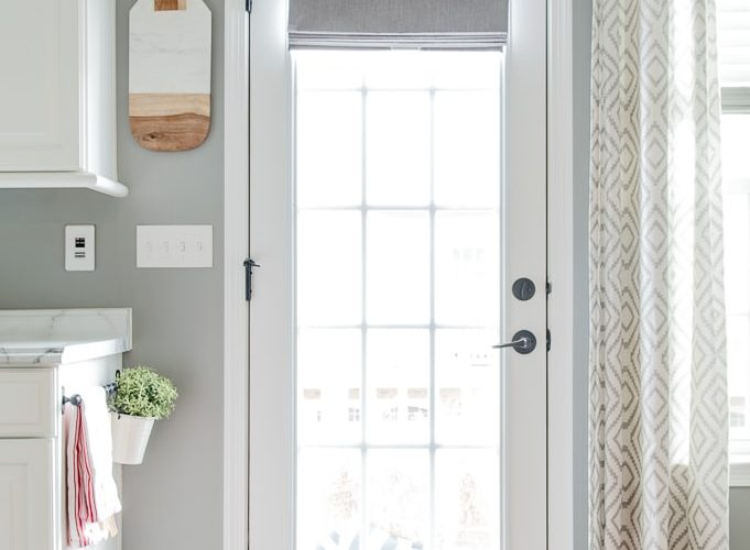 gray roman shade on a french door with light filtering outside mount rolled up