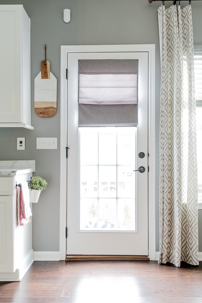 gray roman shade on a french door with light filtering outside mount partially extended top of door