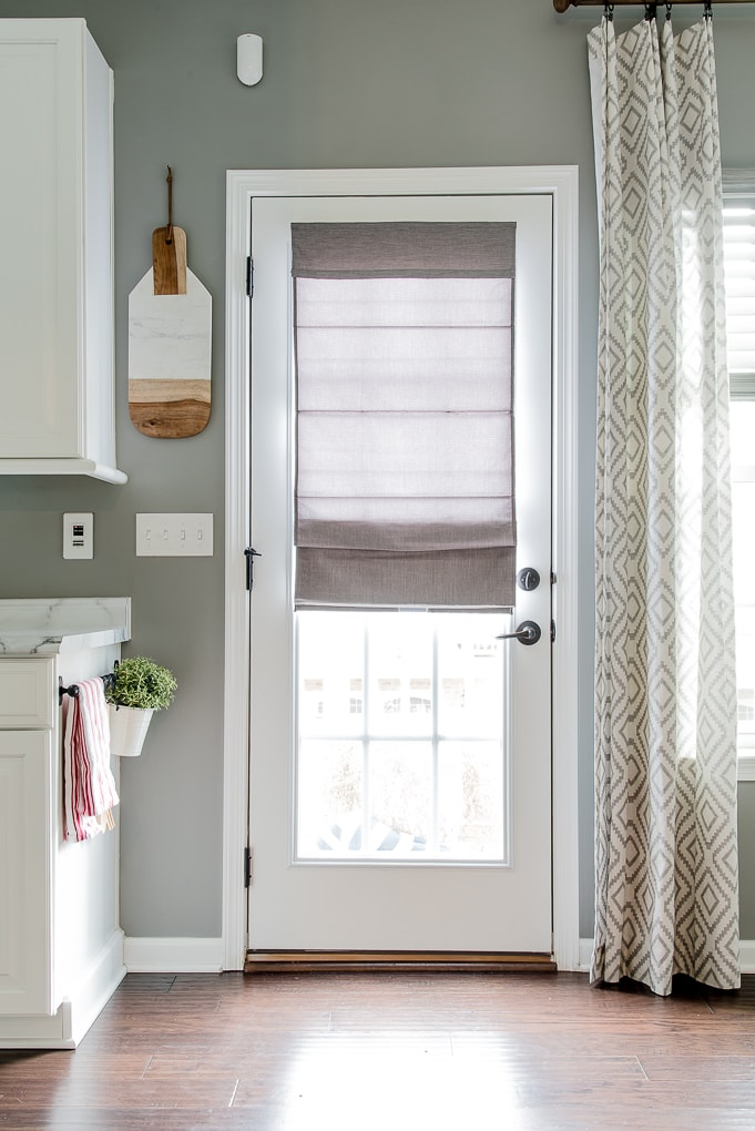 gray roman shade on a french door with light filtering outside mount partially extended bottom of door