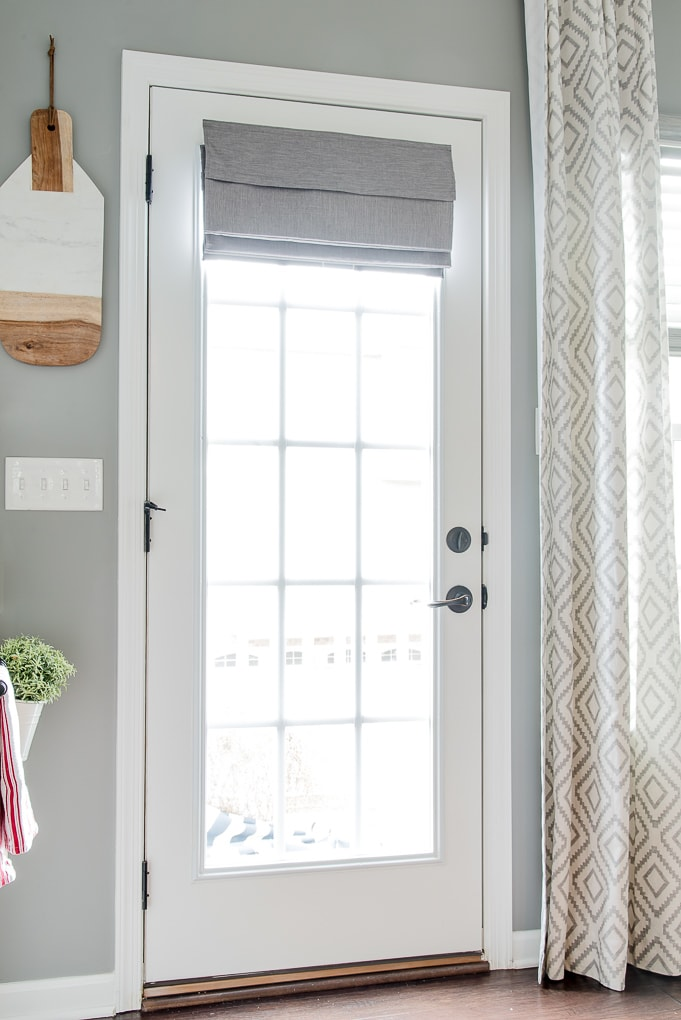 gray roman shade on a french door with light filtering outside mount folded fabric