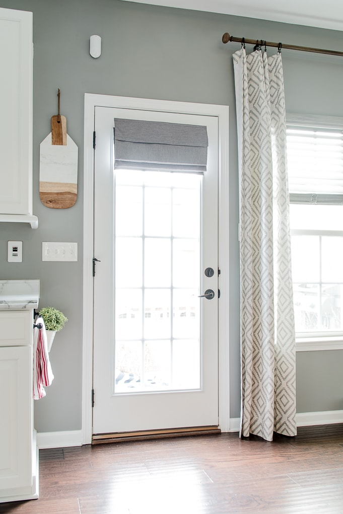 gray roman shade on a french door with light filtering outside mount folded fabric in kitchen