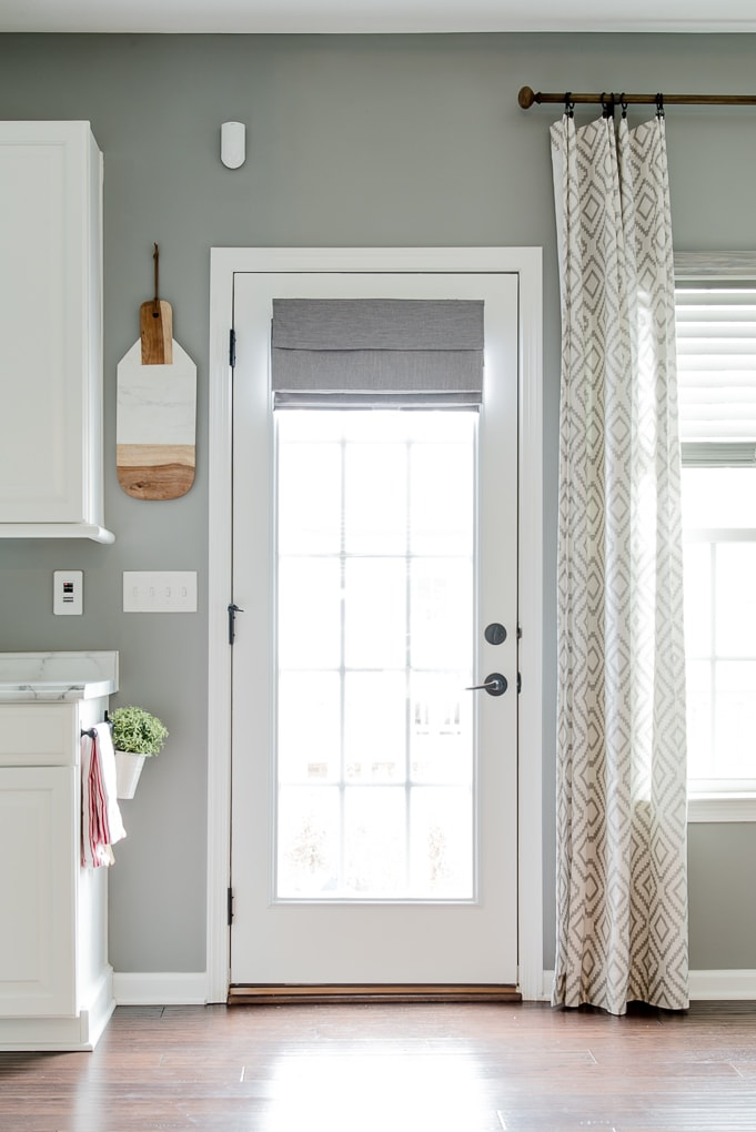 gray roman shade on a french door with light filtering outside mount folded fabric in home leading to porch
