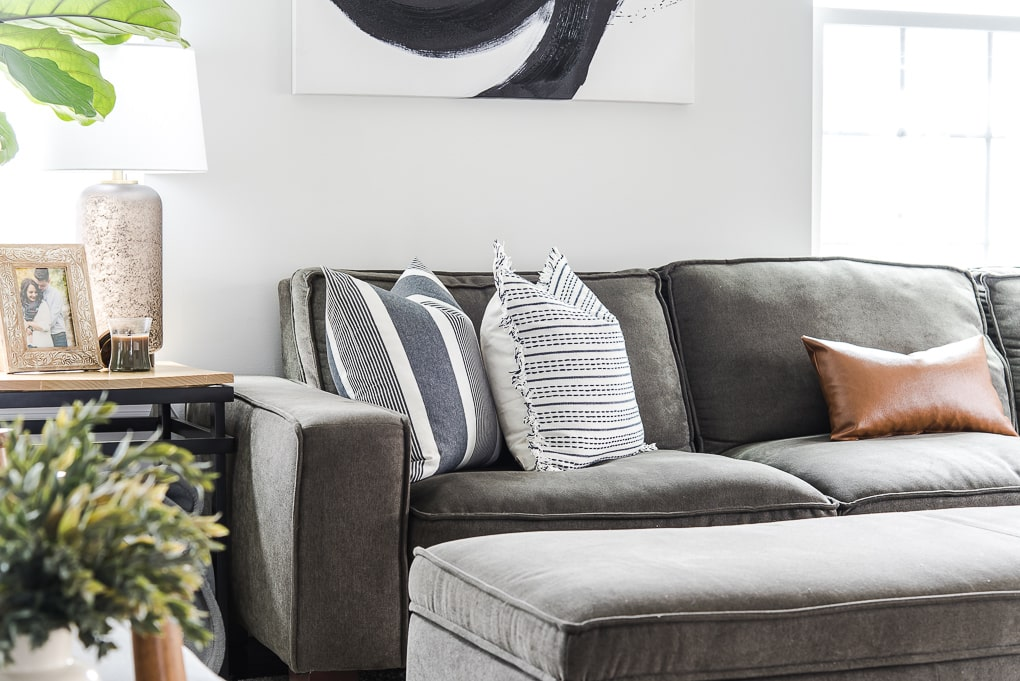 gray couch with blue textured and pattern pillows and brown lumbar pillow