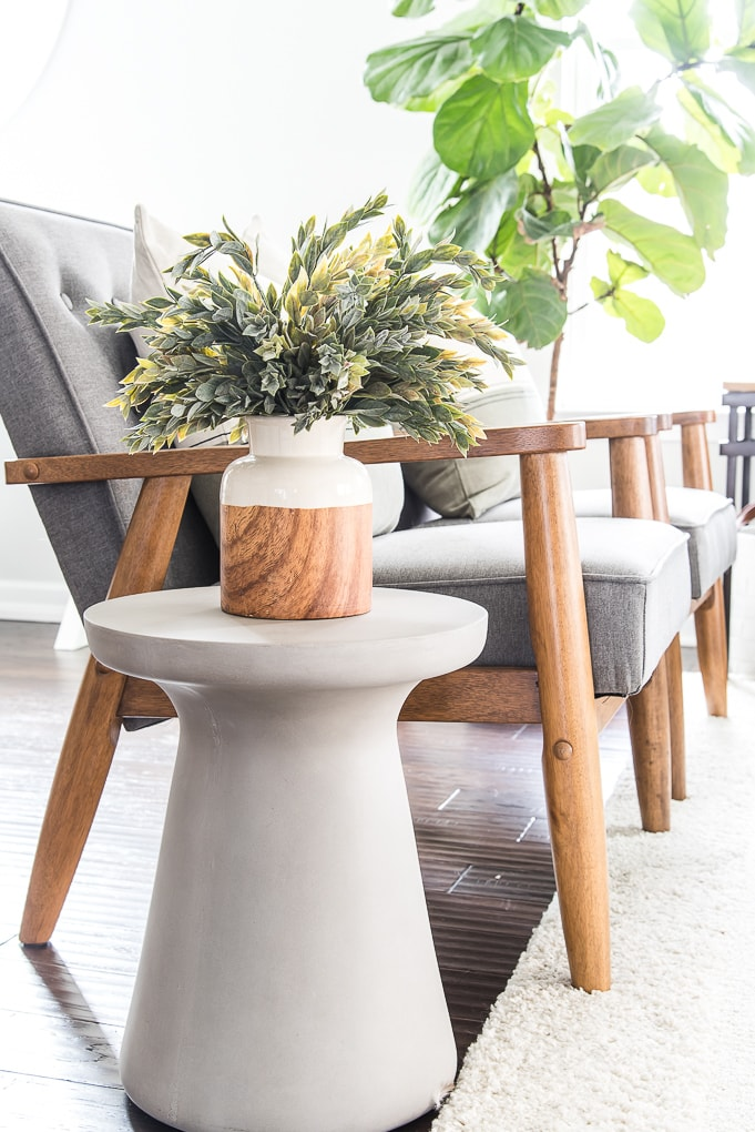 wood and white vase with greenery on a cement side table