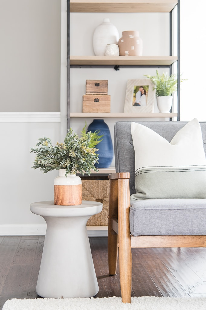 white and wood vase with greenery on a cement side table next to a gray chair