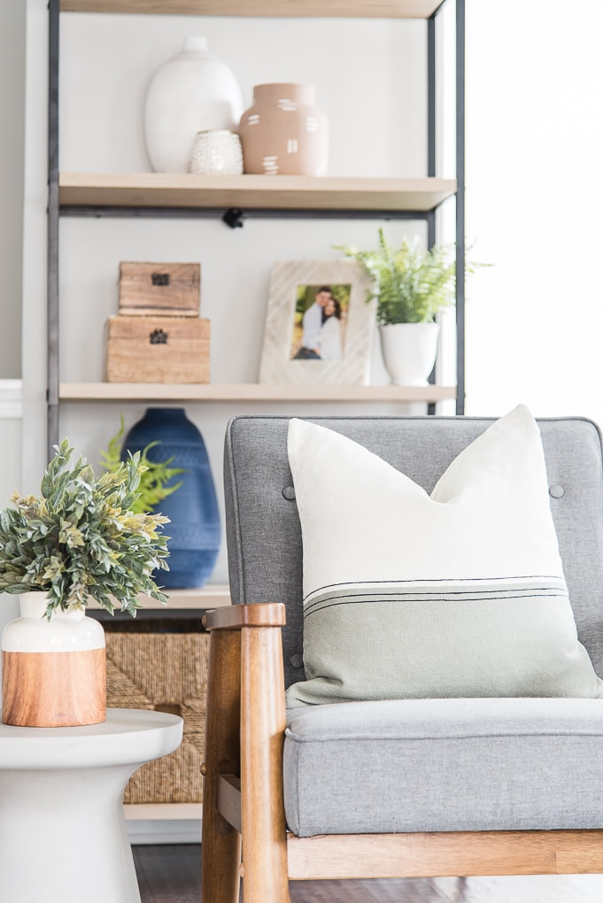 green and white pillow on a gray chair in a living room