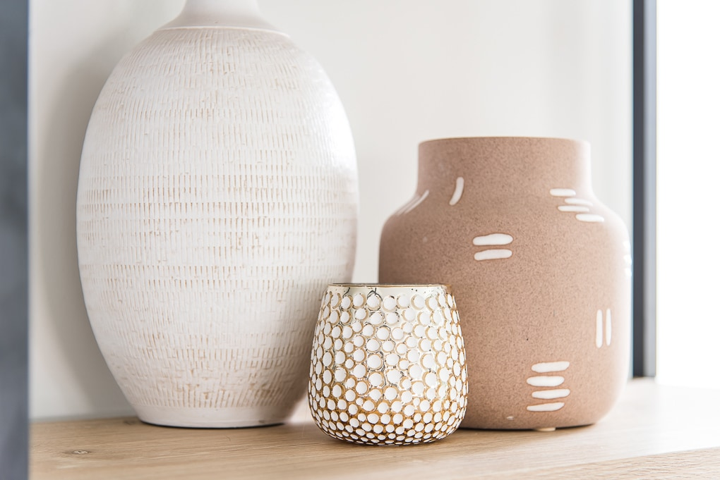 white gold and pink vases textured on a bookshelf