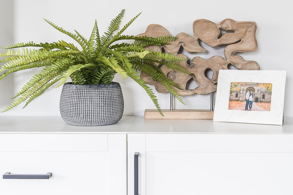 blue vase with faux fern and white marble frame and wooden sculpture on white cabinet