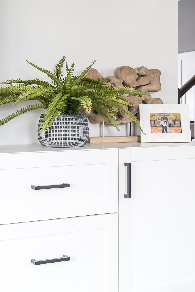 blue vase with faux fern and white marble frame on white cabinet