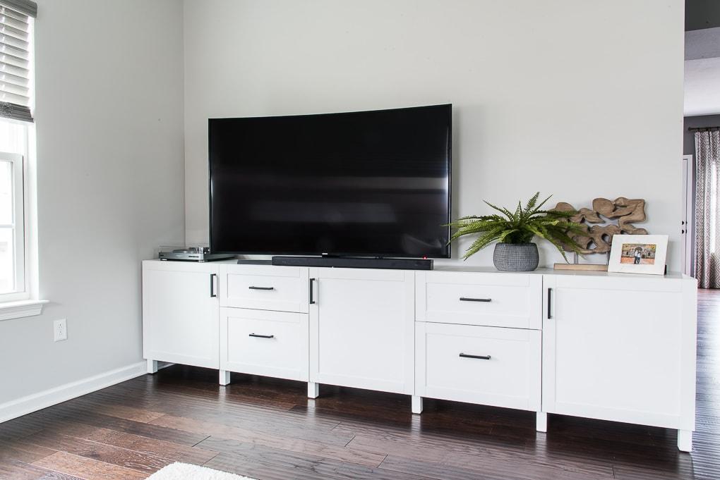 TV on top of white modern media center in a living room