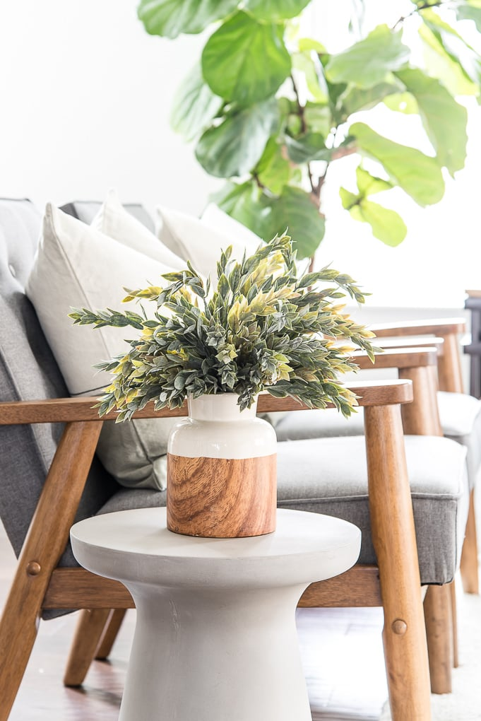 wood and white vase with faux greenery