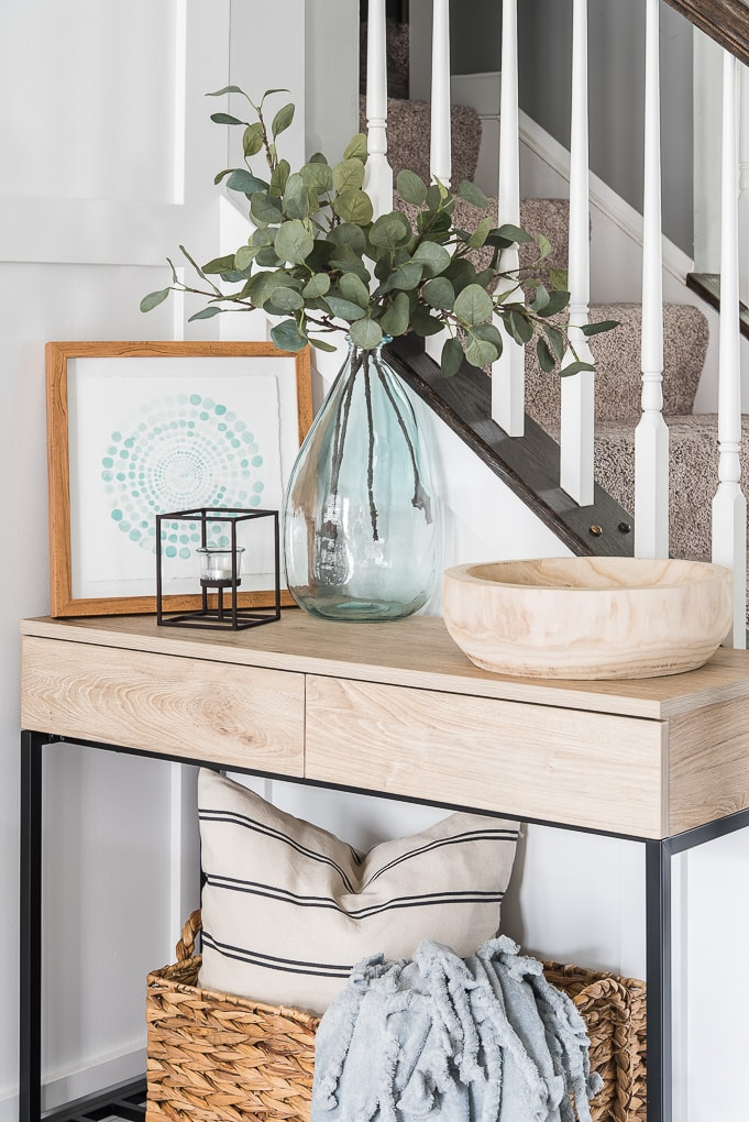 top of a decorated console table for spring with a large vase and greenery