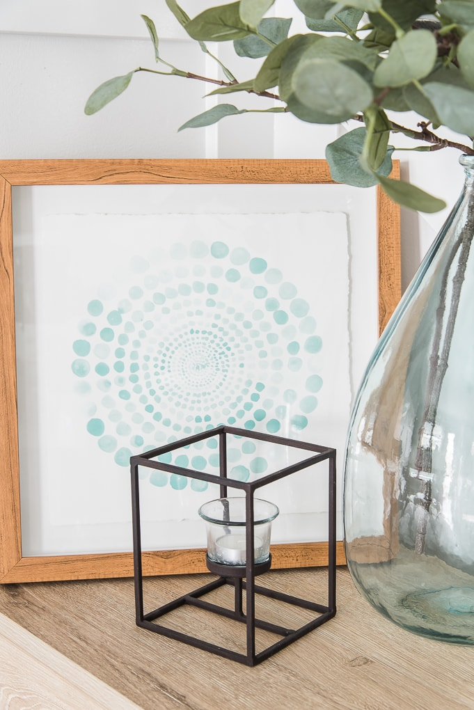abstract blue circle image in a frame and black modern candle holder