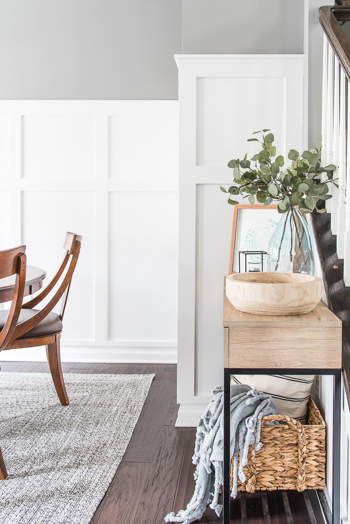 decorated console table in a dining room with white board and batten walls