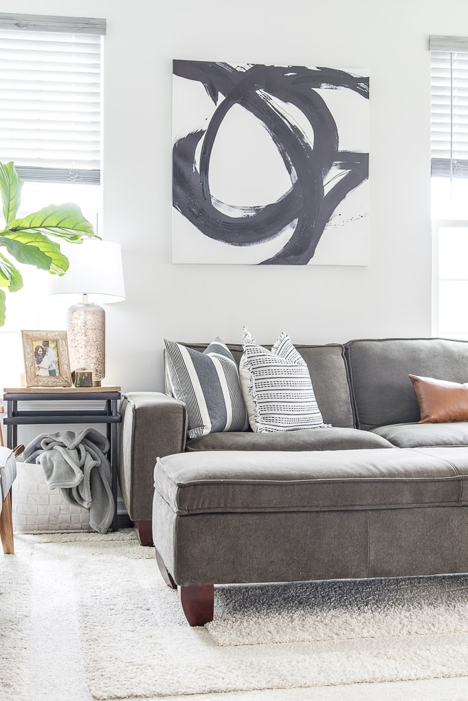 gray couch in living room with modern classic home decorations and pillows