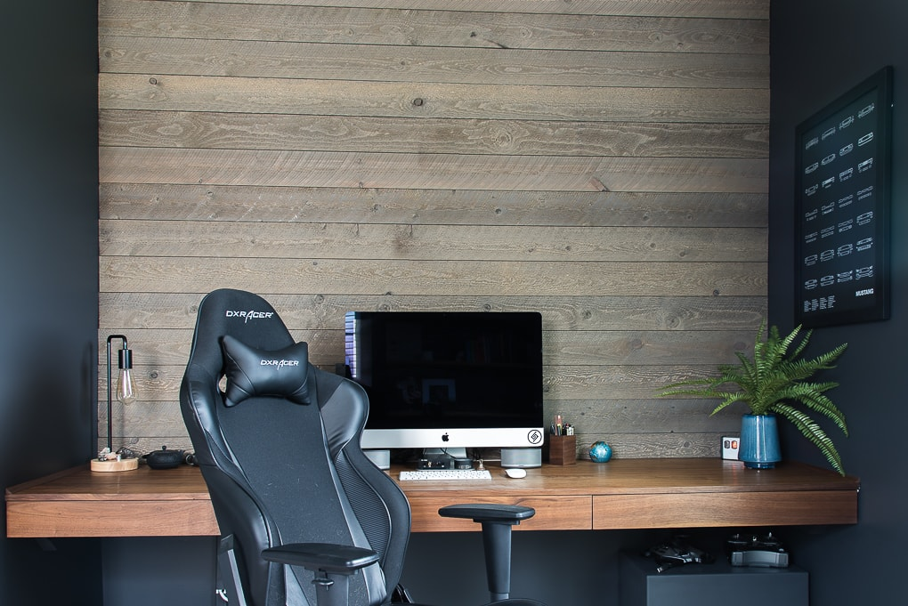 walnut floating desk against wooden pallet wall masculine home office