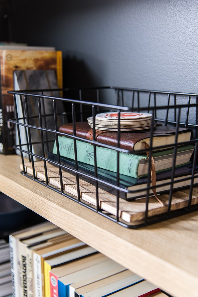wire basket with books on a bookshelf