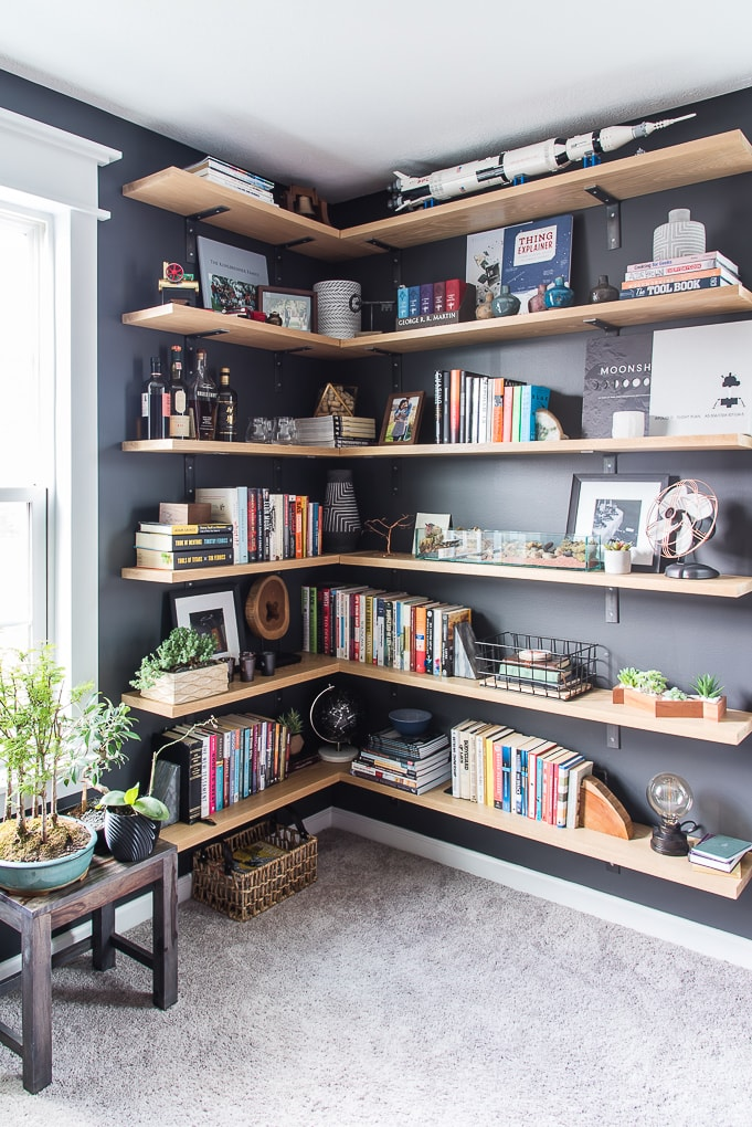 modern industrial floating shelves against a dark wall with books and decorations