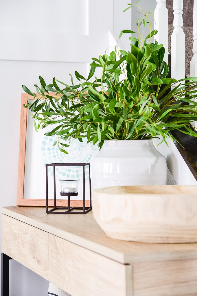 white vase with greenery on natural wood table