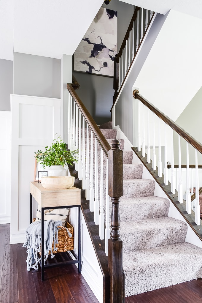 natural wood console table next to staircase with abstract art