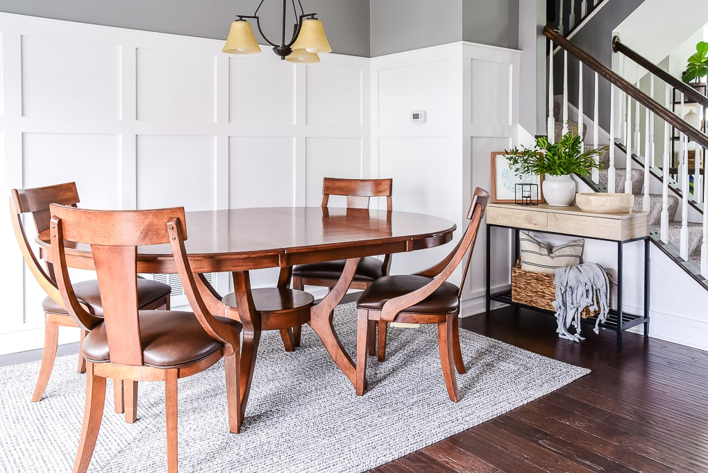 dining room table on gray rug with natural wood console table