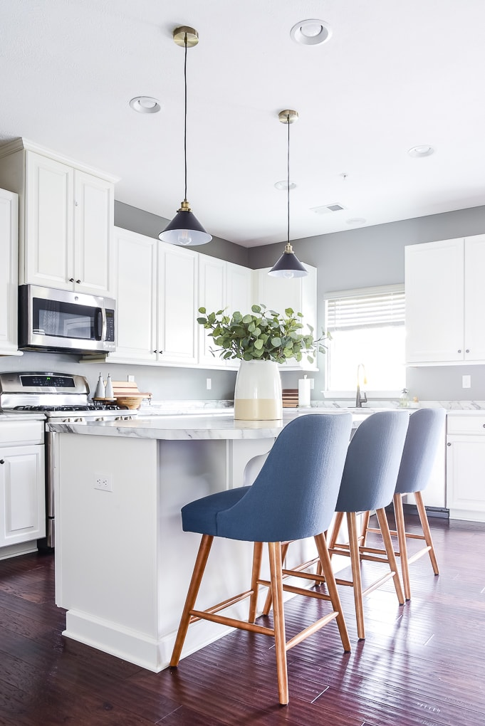 white kitchen with blue barstools and black pendant lights