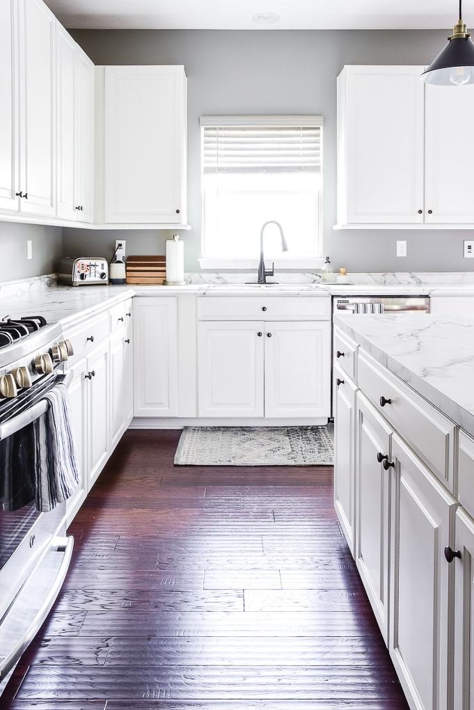 white kitchen cabinets sink and kitchen rug