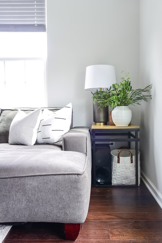 end table with lamp and white vase filled with greenery