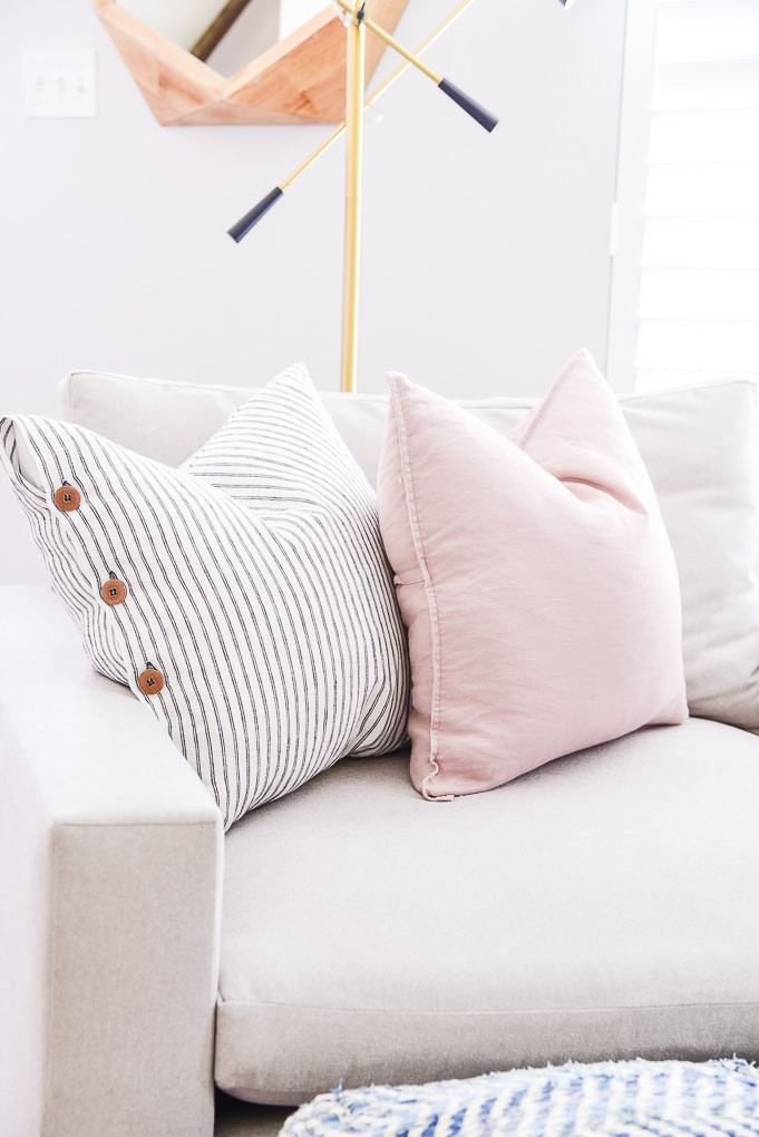 blue striped pillow and pink pillow on an accent chair