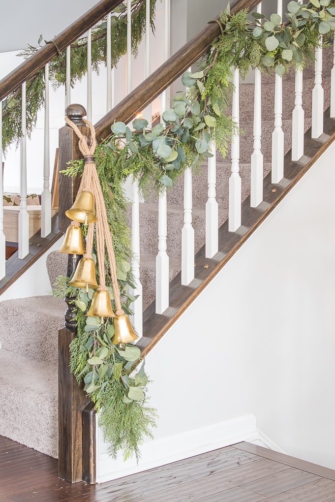 Gold bell Christmas decor on garland on staircase