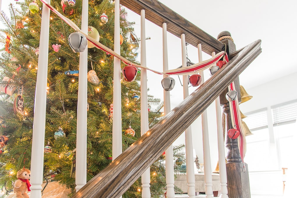 Red and white Christmas bell garland in front of tree