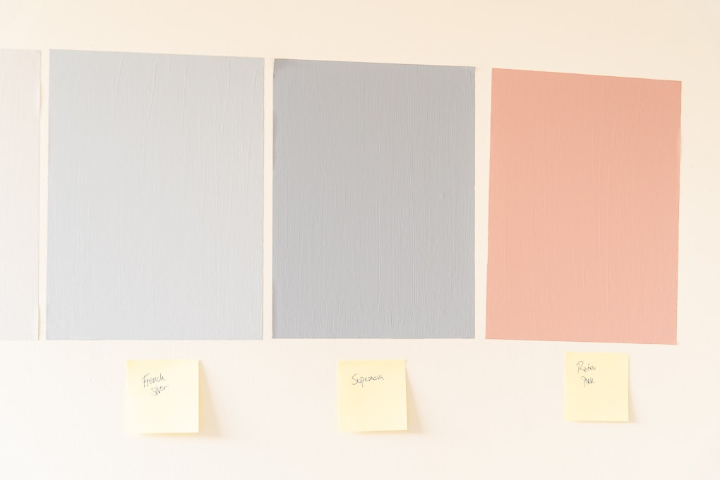 close up of colorful sure swatch paint sample sheets on the wall