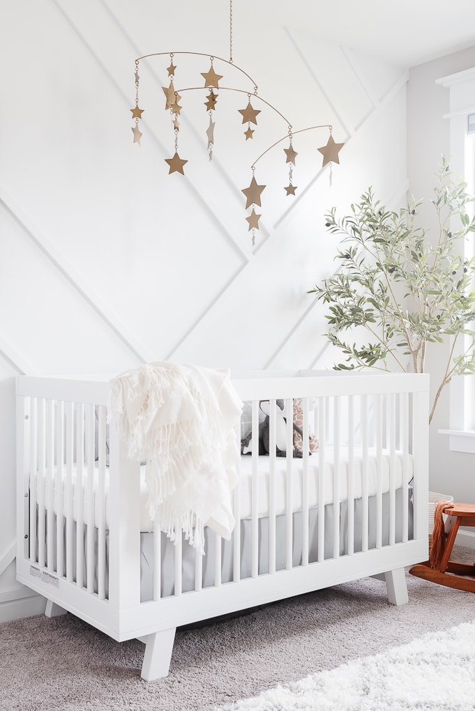 babyletto hudson crib in white against white accent wall and modern gold star mobile from pottery barn kids
