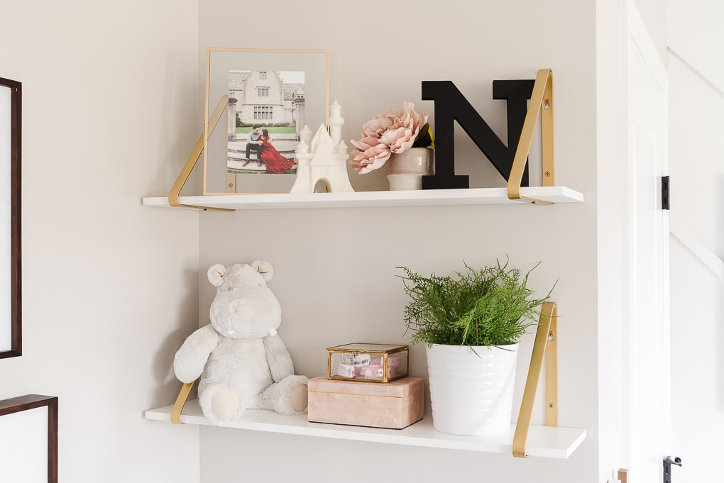 decorative white and gold shelves in a baby nursery