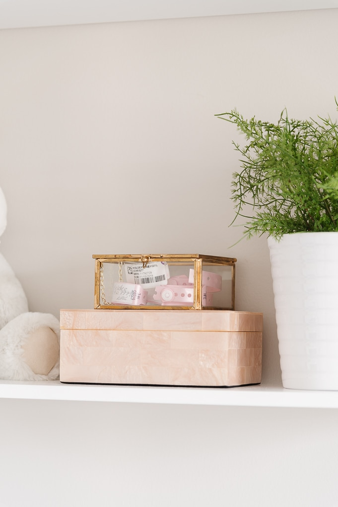decorative boxes and a clear jewelry box with gold edges with baby hospital bands inside
