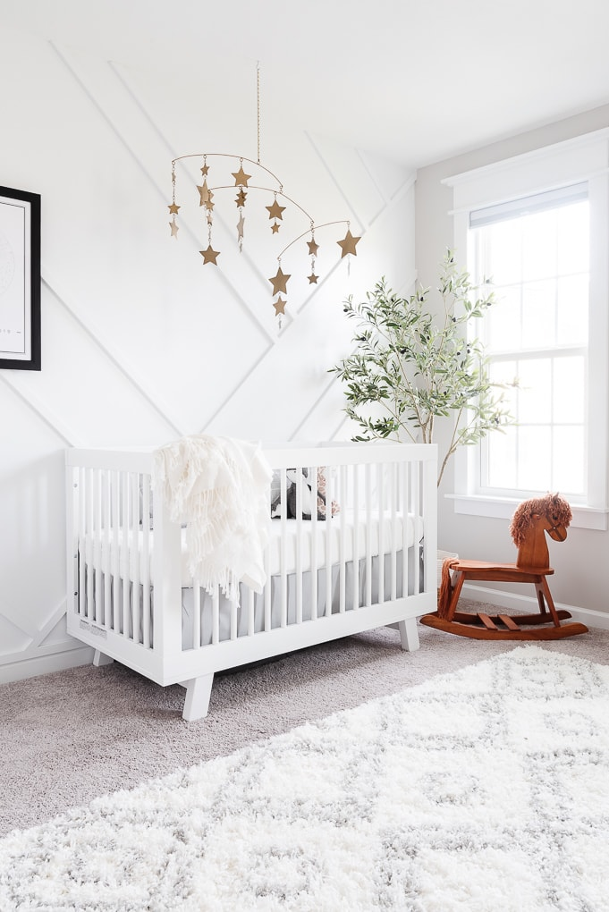 modern neutral feminine nursery with a white crib and a white accent wall